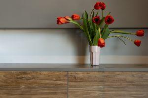 czerwone tulipany w białym wazonie, ustawione na szafce
