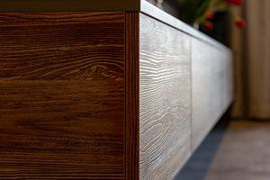 zbliżenie na stolik pod telewizor podkreślające fakturę drewna