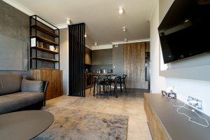 salon oddzielony lamelowym panelem od kuchni