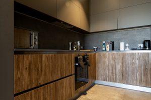 kuchnia o ciemnej kolorystce, z bezuchwytowymi szafkami i nisko osadzonym, zabudowanym piekarnikiem