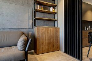 otwarta szafka z książkami w salonie, oddzielona od kuchni czarnym panelem lamelowym