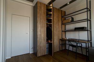 biurko z otwartymi pułkami i podświetlana szafa na ubrania o kolorze drewna