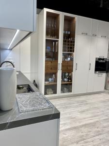 kuchnia z jasnymi panelami podłogowymi i pojemną, przeszkloną szafą