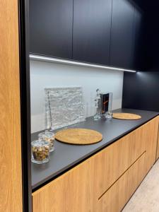 meble kuchenne o kolorach czerni i drewna, z oświetleniem led zamontowanym pod szafkami