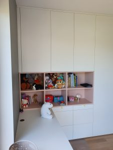 białe meble z różowymi pułkami w pokoju dziecinnym