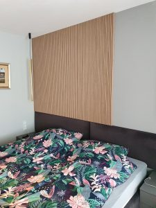 łózko w sypialni i panelami ściennymi - lamelami