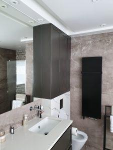łazienka z oświetleniem w suficie i jednolitym, płaskim, czarnym, dekoracyjnym grzejnikiem